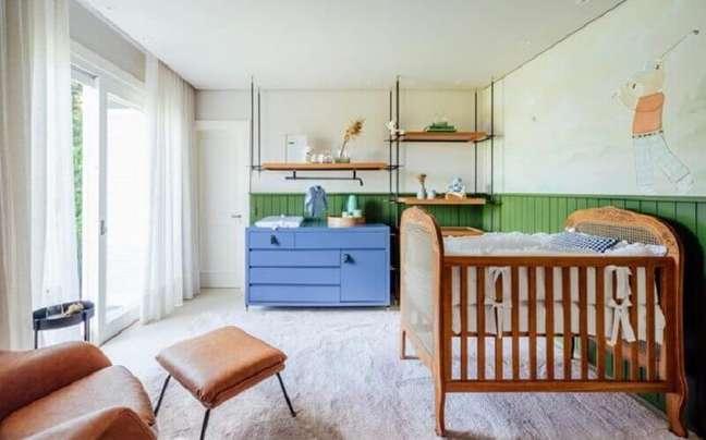 30. Berço de madeira simples para quarto de bebê decorado com cômoda azul e meia parede verde – Foto: Greisse Panazzolo