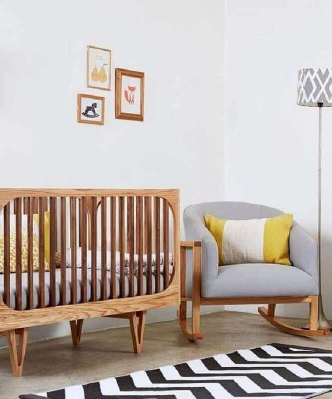 36. Decoração clean para quarto de bebê com poltrona cinza e berço de madeira – Foto: Love Property