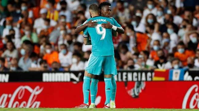 Vinicius Junior e Benzema, autores dos gols do Real, se abraçam na vitória deste domingo