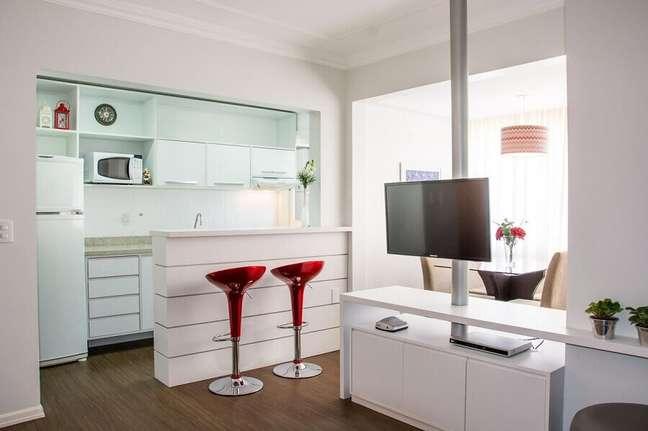 29. Decoração com banqueta vermelha para sala e cozinha americana toda branca – Foto: Elisangela Cardoso de Almeida