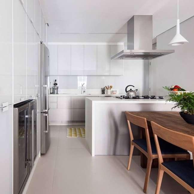 52. Mesa de madeira para decoração clean de sala e cozinha americana branca – Foto: Iná Arquitetura