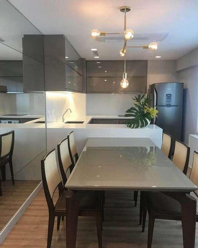 41. Decoração moderna em tons de cinza para sala e cozinha americana integradas com mesa planejada junto a bancada – Foto: Manuela Senna Arquitetura