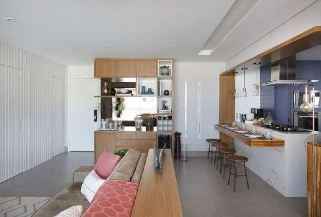 21. Casa com sala e cozinha americana decorada com bancada de madeira planejada em ilha de mármore – Foto: Bianchi e Lima Arquitetura