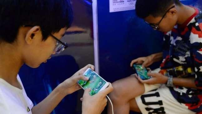 Garotos jogam Honor of Kings, jogo mobile distribuído pela Tencent, durante evento em Shopping Center na China