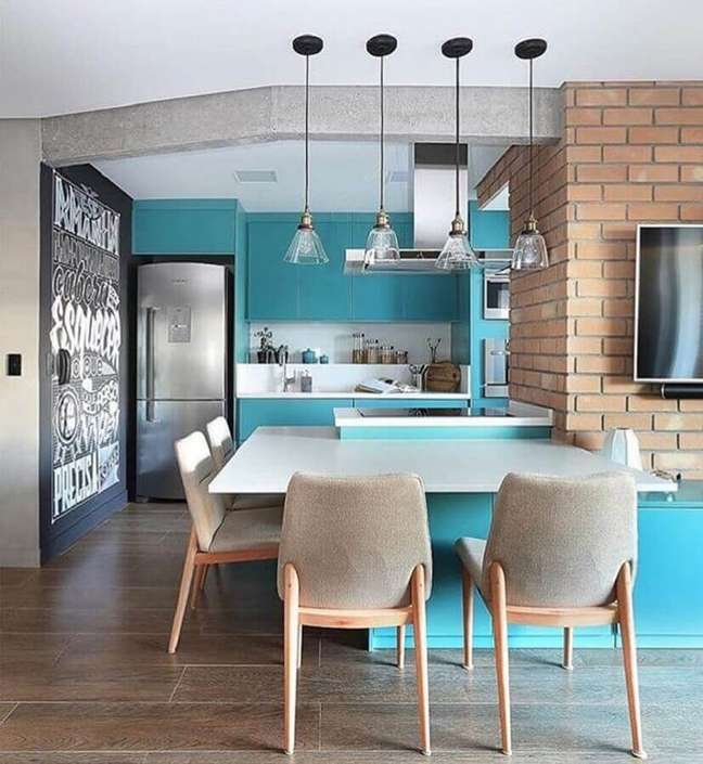 5. Azul turquesa para decoração de sala e cozinha americana com parede de tijolinho – Foto: Quattrino Arquitetura