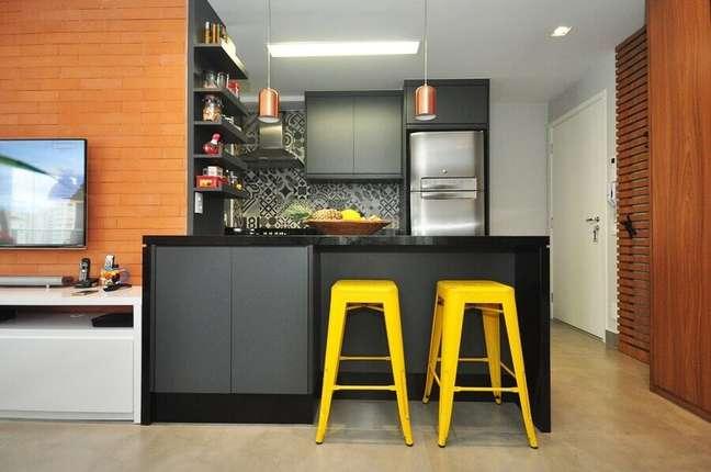 55. Parede de tijolinho para decoração de sala e cozinha americana com banqueta amarela – Foto: Condecorar Arquitetura e Interiores
