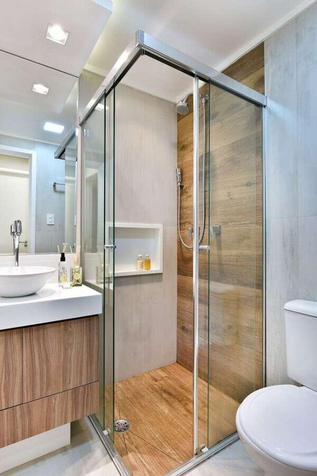 45. Decoração simples para banheiro com piso de madeira no box e gabinete pequeno suspenso – Foto: Tetriz Arquitetura