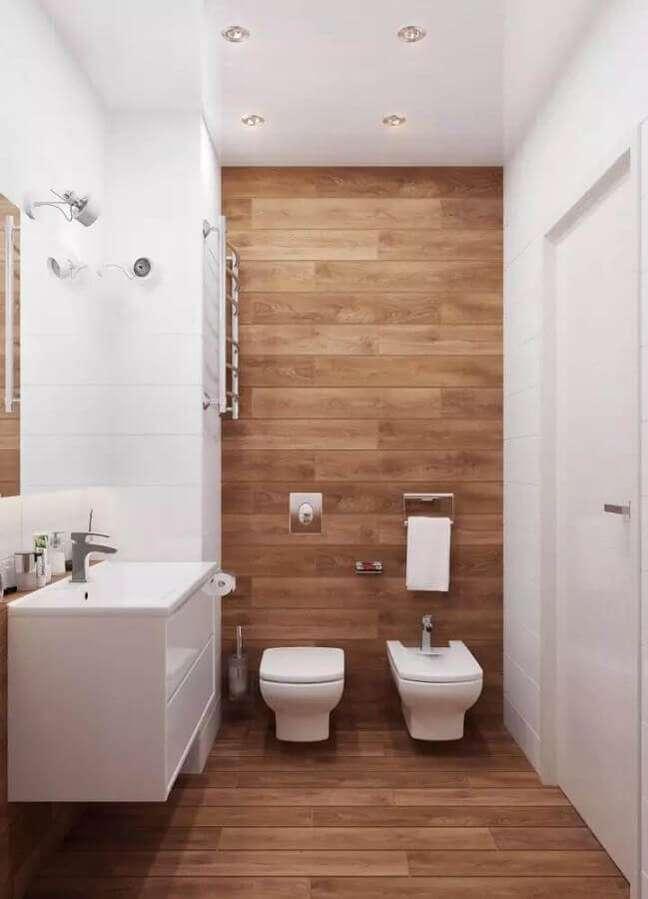 27. Decoração de banheiro com piso de madeira e gabinete branco pequeno – Foto: Valeru Anka