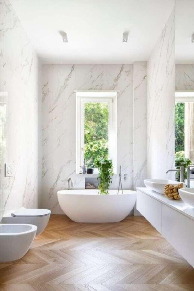 54. Parede de mármore para decoração de banheiro com piso de madeira e banheira de imersão – Foto: HomeAdore
