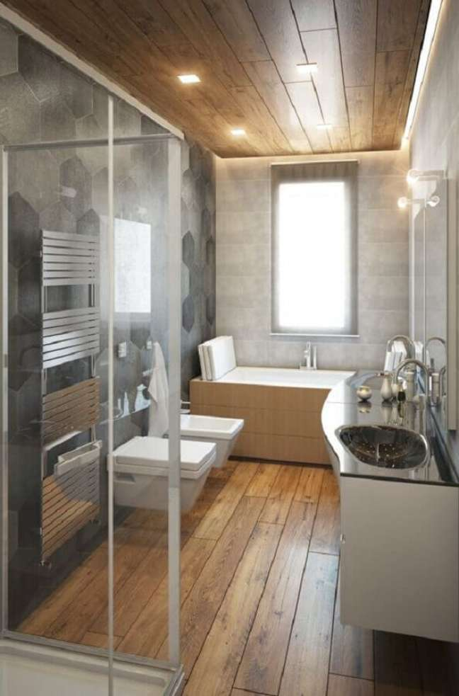 57. Revestimento cinza hexagonal para decoração moderna de banheiro com piso de madeira – Foto: Voglia di Ristrutturare