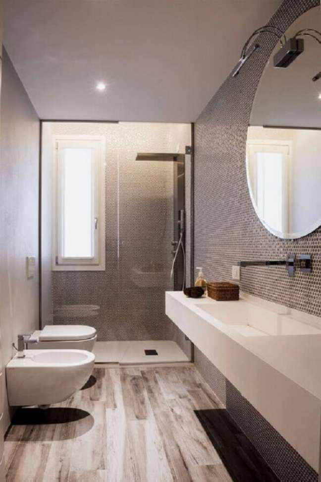 42. Decoração moderna para banheiro com piso de madeira e espelho redondo bisotado – Foto: Voglia di Ristrutturare