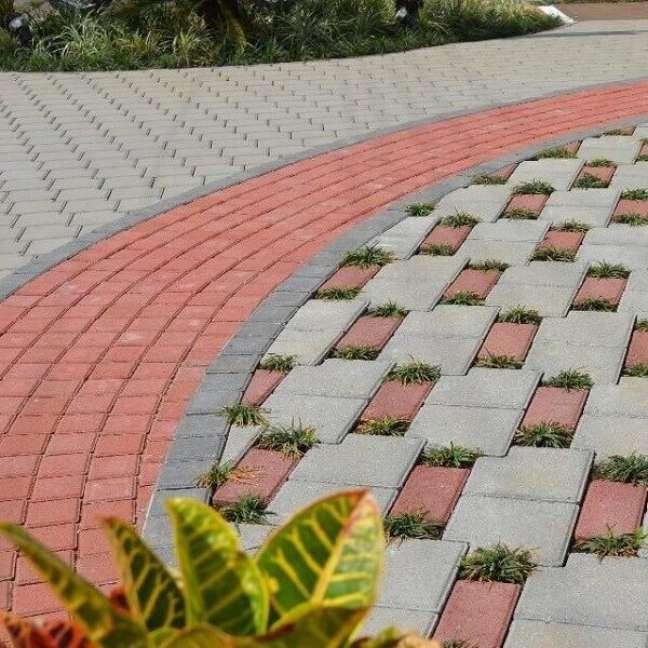 27. O piso intertravado vermelho forma lindas composições no chão da área externa com jardim. Fonte: Betonart Concretos