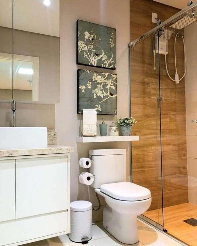 55. Quadros para decoração de banheiro com piso de madeira no box – Foto: Luana Giusti