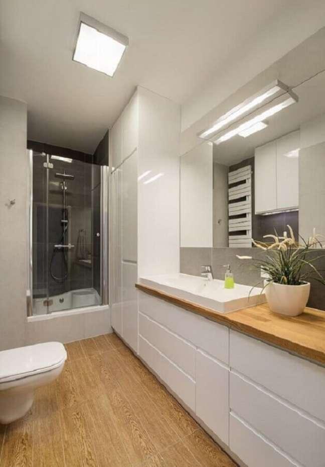 9. Armário planejado para decoração de banheiro pequeno com piso de madeira – Foto: Homebook