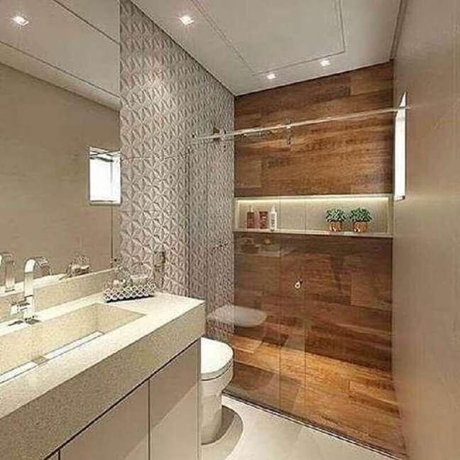 56. Revestimento 3D para decoração de banheiro com piso de madeira no box – Foto: Fênix Engenharia e Arquitetura