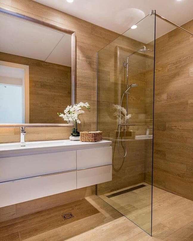 49. Gabinete branco suspenso para decoração de banheiro com piso de madeira – Foto: Home Fashion Trend