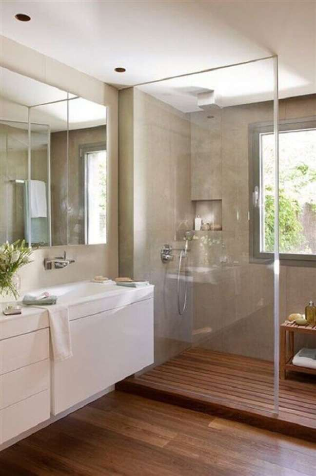 15. Banheiro com piso de madeira decorado com parede de cimento queimado – Foto: Casa e Jardim