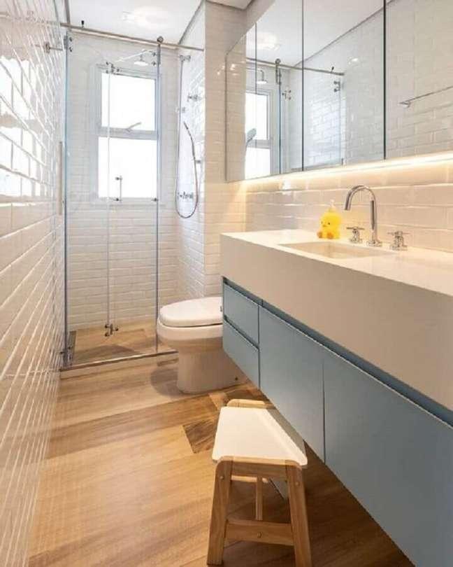 18. Banheiro pequeno com piso de madeira decorado com metro white e gabinete azul pastel – Foto: Marina Carvalho