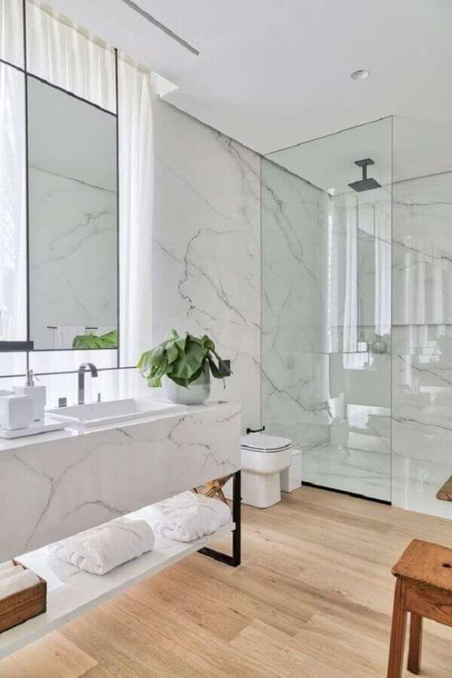 8. Decoração de luxo para banheiro com piso de madeira e bancada de mármore – Foto: HomeAdore
