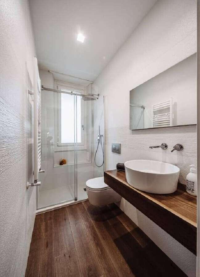 4. Decoração de banheiro pequeno com piso de madeira e espelho sem moldura – Foto: HomeAdore