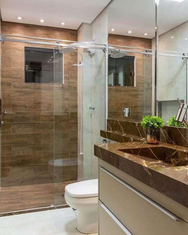 10. Bancada de mármore marrom para decoração de banheiro com piso de madeira Foto Emily Streck