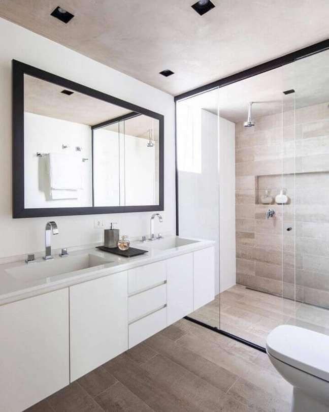 28. Decoração de banheiro com piso de madeira e gabinete branco suspenso – Foto: Conrado Ceravolo