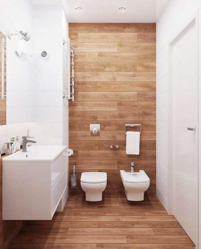 21. Decoração clean para banheiro com piso de madeira e gabinete branco pequeno – Foto: Decor Fácil