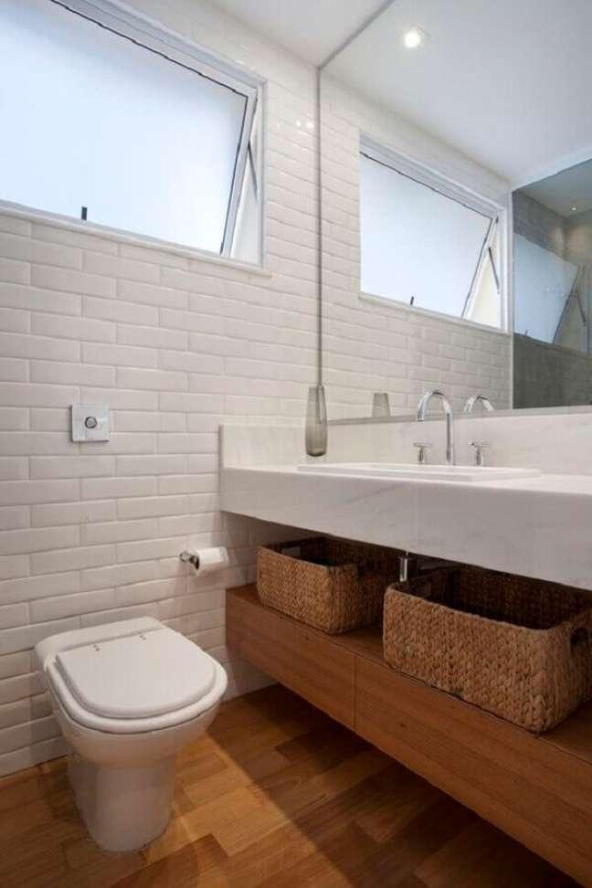 14. Banheiro com piso de madeira decorado com metro white e bancada de mármore – Foto: Escritorio InTown