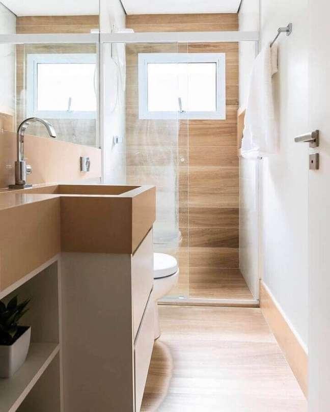 17. Banheiro pequeno com piso de madeira decorado com gabinete e bancada planejada – Foto: CW Arquitetura e Design