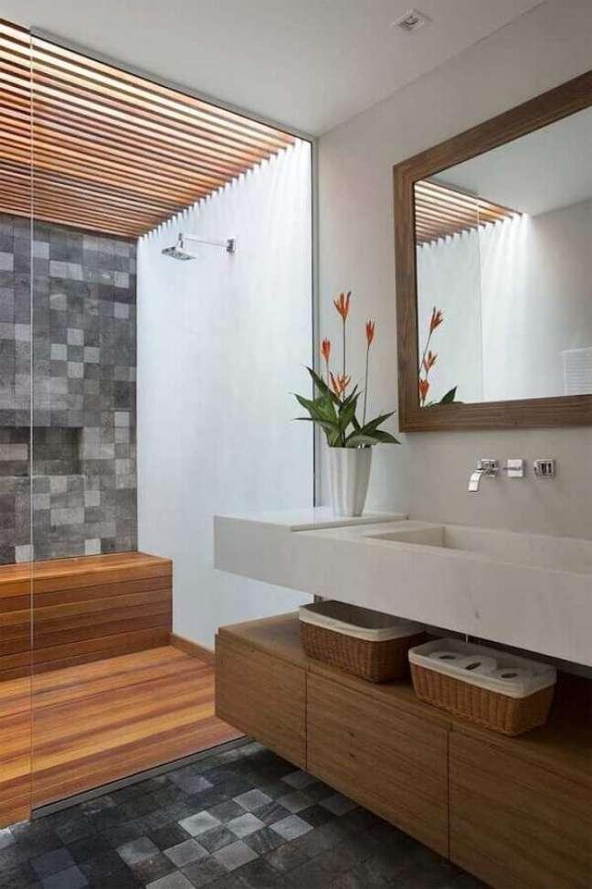 16. Banheiro com piso de madeira no box decorado com revestimento cinza quadriculado – Foto: Tripper Arquitetura