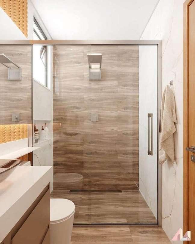 44. Decoração moderna para banheiro pequeno com piso de madeira – Foto: Paloma Rodrigues