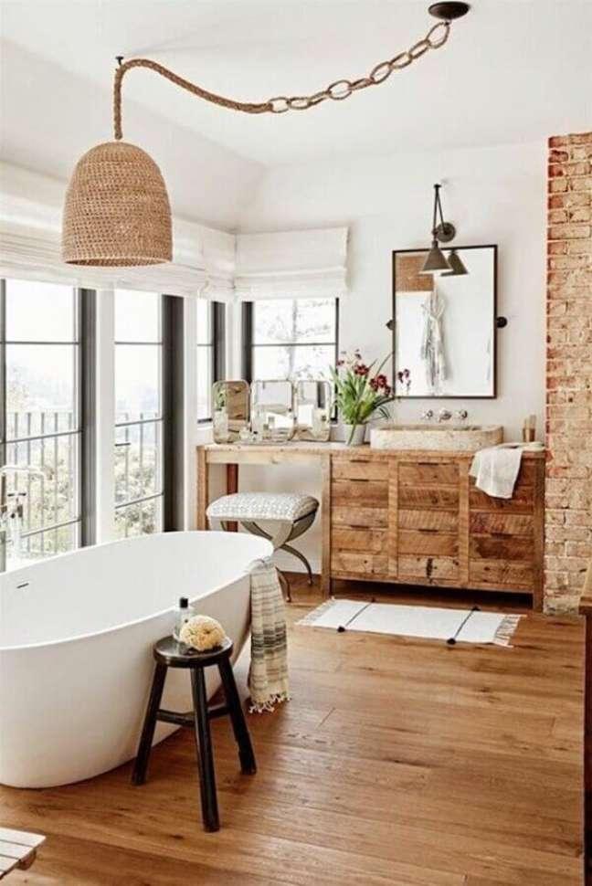 51. Lustre rústico para decoração de banheiro com piso de madeira e banheira de imersão – Foto: Clem Around The Corner