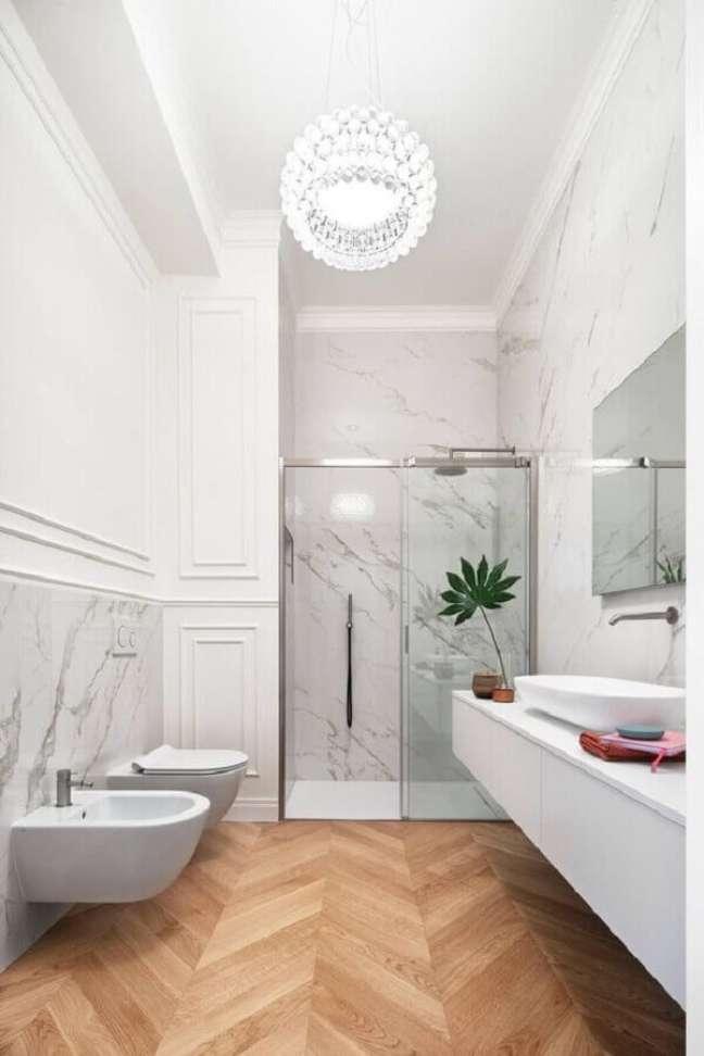 13. Banheiro com piso de madeira decorado com boiserie e meia parede de mármore – Foto: HomeAdore