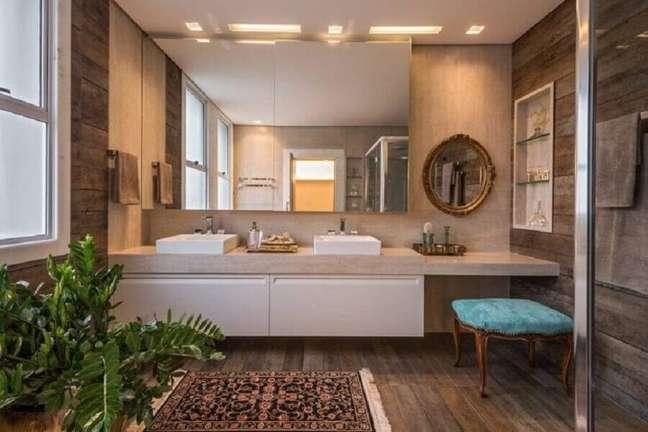 11. Bancada planejada com penteadeira para decoração de banheiro com piso de madeira – Foto: Izabela Dinelli