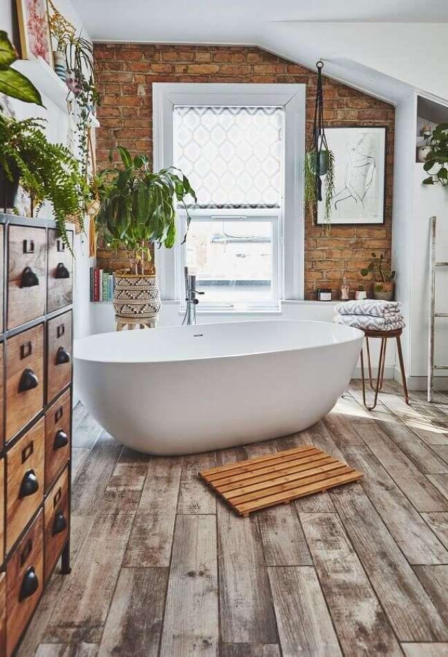12. Banheira de imersão para decoração de banheiro com piso de madeira e parede de tijolinho à vista – Foto: Real Homes