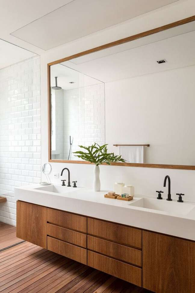 50. Gabinete suspenso para banheiro com piso de madeira decorado com metro white – Foto: Studio Kos
