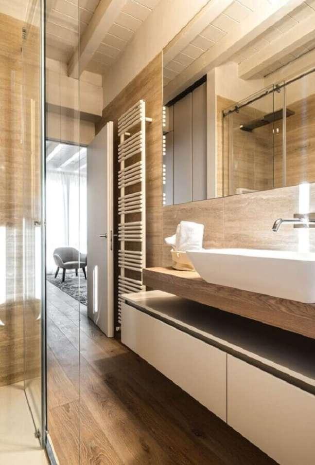 36. Decoração moderna com gabinete planejado para banheiro com piso de madeira – Foto: Decor Fácil