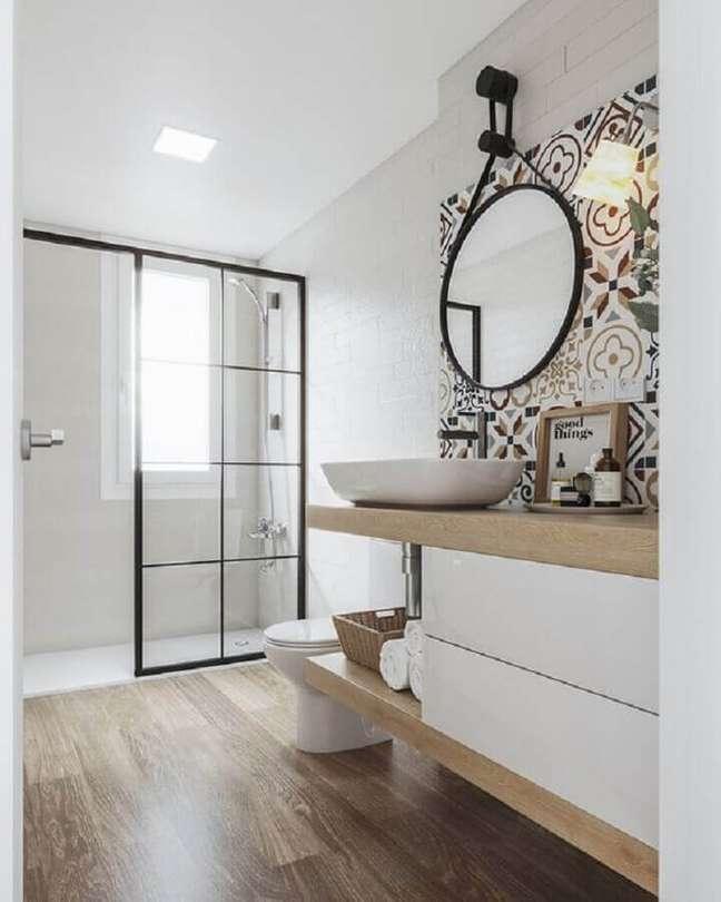 48. Espelho redondo e ladrilho hidráulico para decoração de banheiro com piso de madeira – Foto: Iglû Estúdio