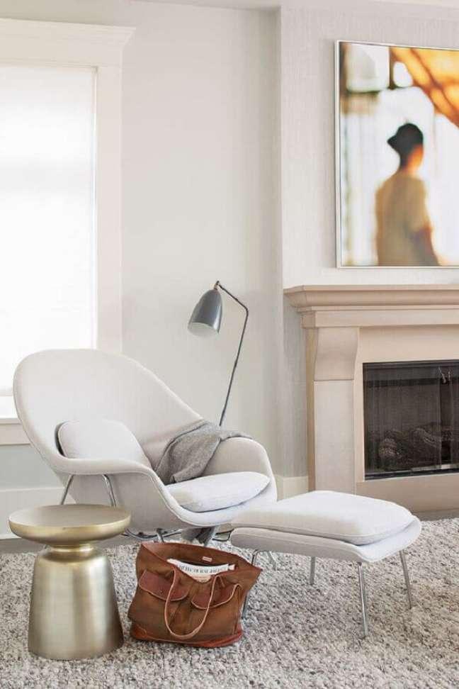 9. Decoração moderna com poltrona branca para sala com lareira – Foto: HomeAdore