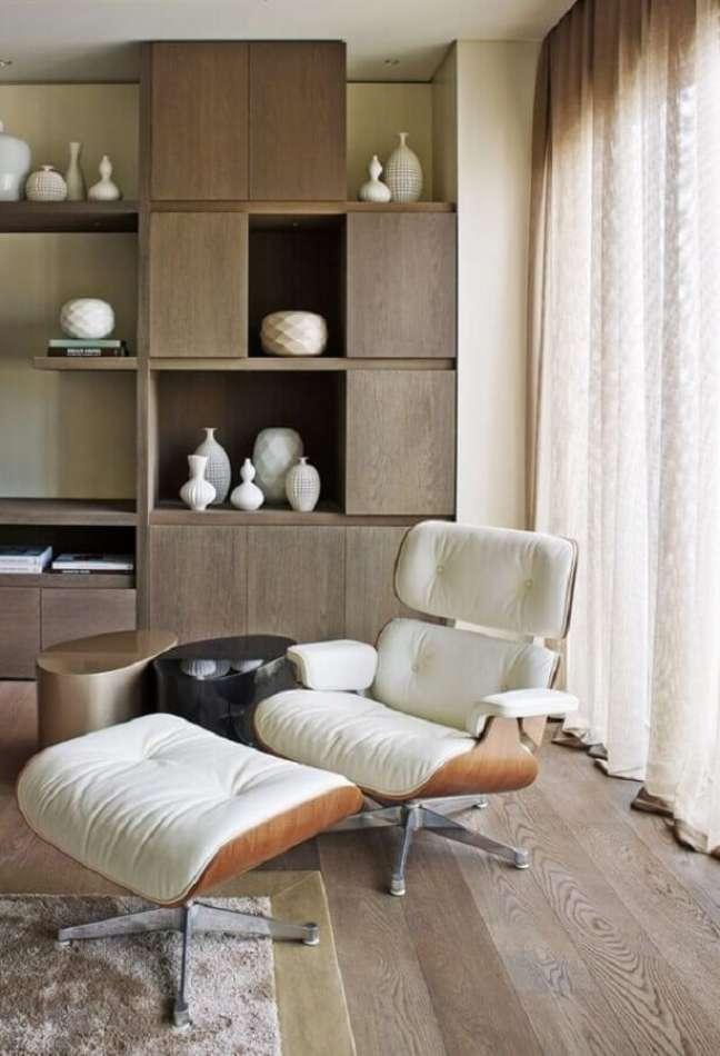 21. Decoração de sala com estante de madeira e poltrona eames branca – Foto: Architectural Digest
