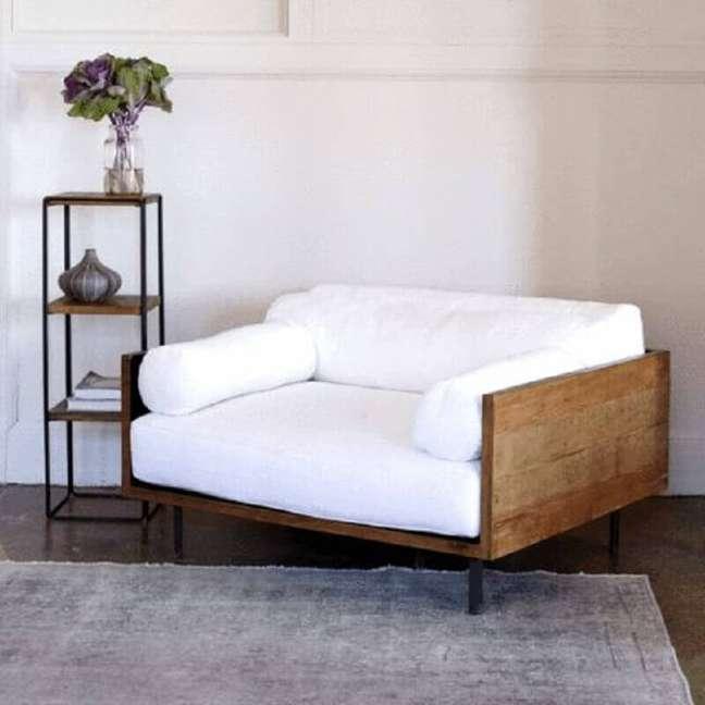 31. Poltrona branca com madeira confortável para sala decorada com tapete cinza e estante pequena Foto Adore Magazine