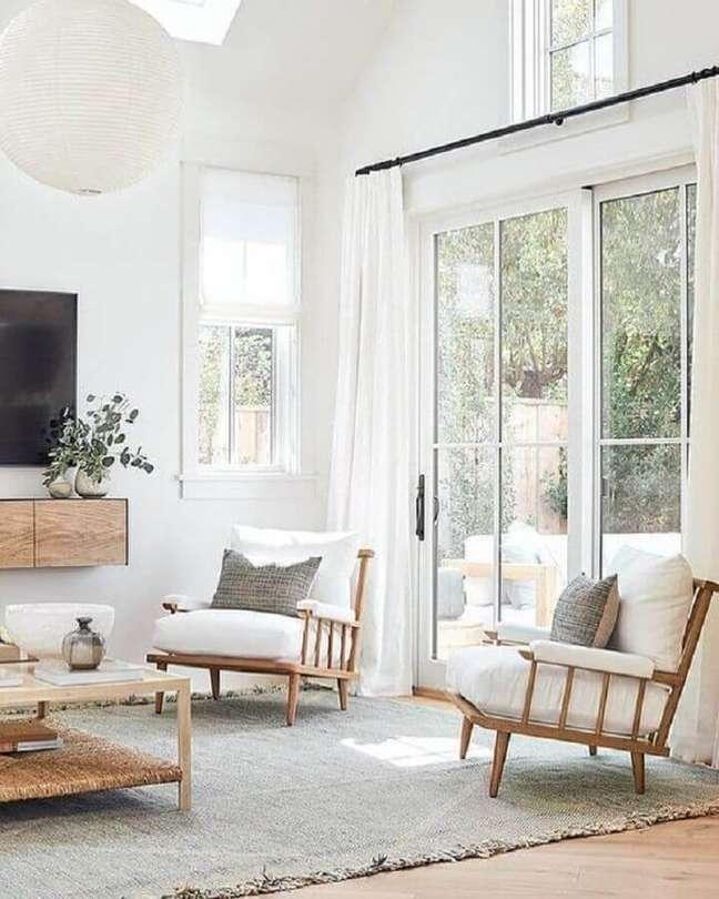 6. Sala de TV decorada com lustre redondo e poltrona branca com madeira – Foto: Studio McGee