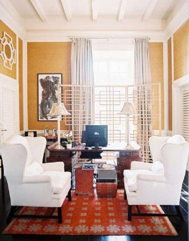 18. Decoração de escritório com parede amarela e poltrona branca – Foto: Lonny Magazine