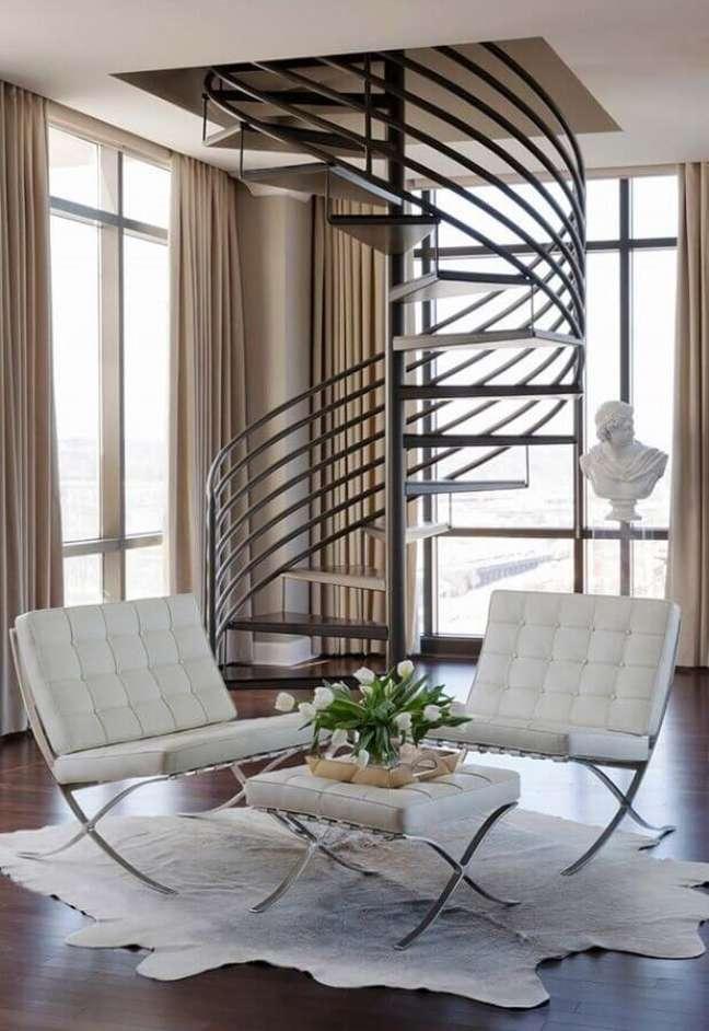 50. Poltrona branca para sala decorada com tapete de couro e escada caracol – Foto: Decor Fácil