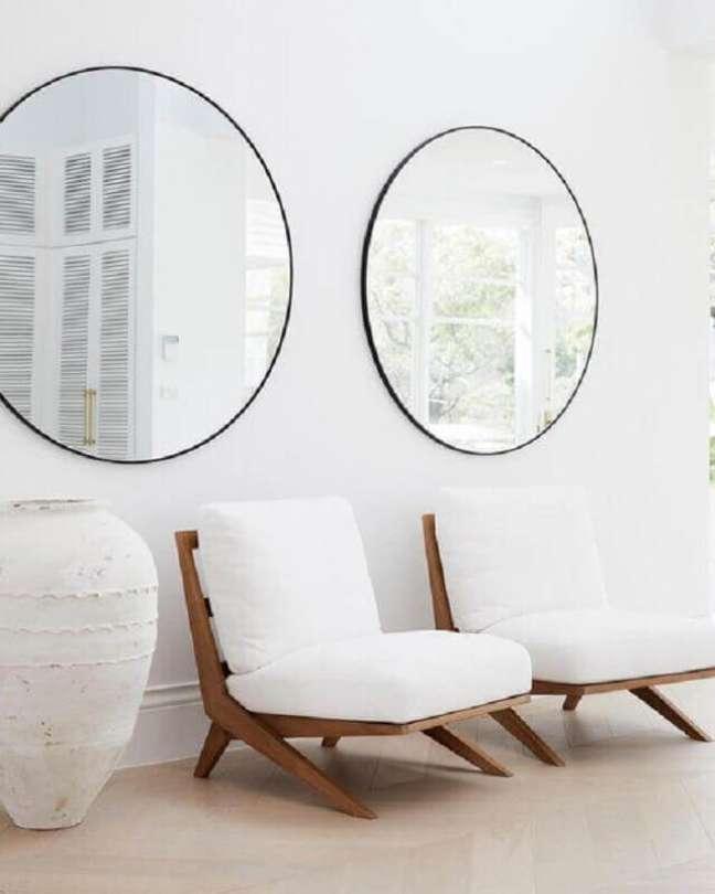 45. Poltrona branca para sala de estar decorada com espelho redondo – Foto: Three Birds Renovations