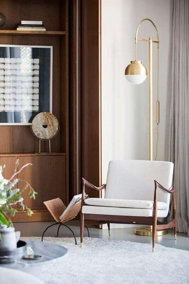 30. Poltrona decorativa branca para decoração de sala com luminária de piso e estante de madeira – Foto: Behance