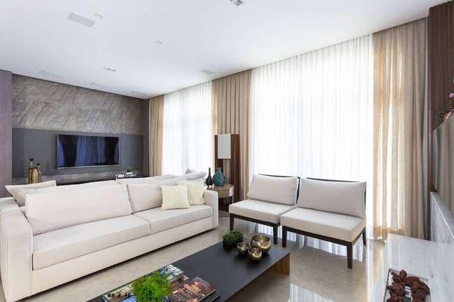 53. Poltrona branca para sala moderna decorada com painel para TV – Foto: Alex Bonilha