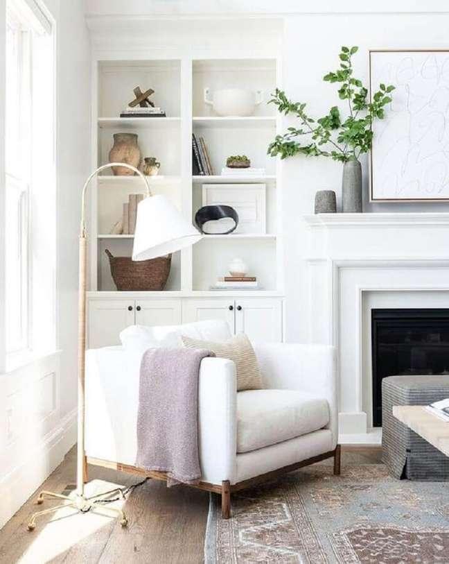 44. Poltrona branca para sala com lareira decorada com luminária de piso e estante planejada – Foto: McGee e Co.