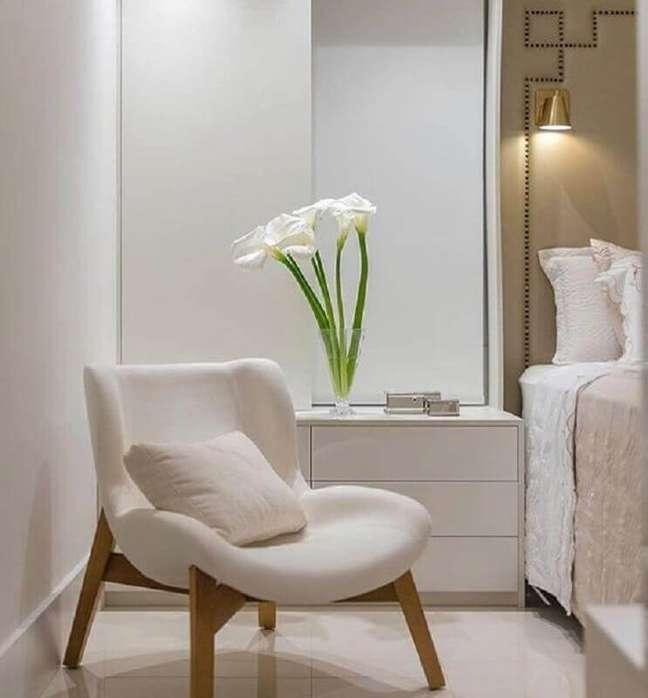 10. Cores neutras para quarto decorado com poltrona branca e luminária de parede – Foto: Decor Fácil