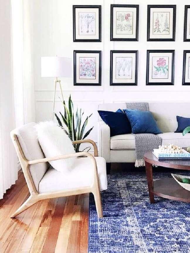 59. Sofá e poltrona branca para sala decorada com mural de quadros e almofadas azuis – Foto: Essential Home